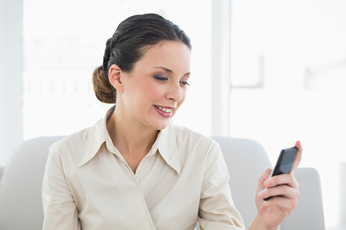 professional woman smiles at her phone will doing research